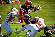 Logan Granera '13 leaps over two Macalester defenders during Saturday's 45-35 home opener win at Grinnell College.
