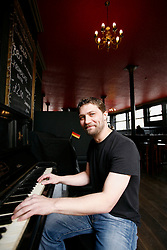 UK ENGLAND LONDON 13MAR12 - Juergen Maennel, owner of the Zeitgest Gastro-pub poses for a picture at the German-made piano once played by Charlie Chaplin's father. The Zeitgest, located at The Jolly Gardener pub in Lambeth near the river Thames offers a good selection of German food and beverages.....jre/Photo by Jiri Rezac....© Jiri Rezac 2012
