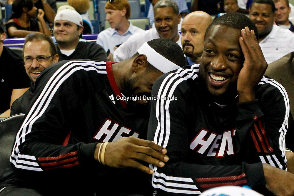 October 13, 2010; New Orleans, LA, USA; Miami Heat small forward LeBron James (6) and shooting guard Dwyane Wade (3) laugh from the bench during the second half of a preseason game against the New Orleans Hornets at the New Orleans Arena. The Hornets defeated the Heat 90-76. Mandatory Credit: Derick E. Hingle