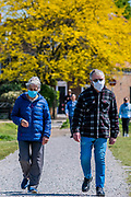 Confusion over masks remains to be clarified, as an older couple, apparentltly, pontlessly wear masks on her outdoor walk. Fit older people make their own decision on whether to stay locked down - All ages enjoy the opportunity to exercise on Wimbeldon Common as the sun is out. The 'lockdown' continues for the Coronavirus (Covid 19) outbreak in London.