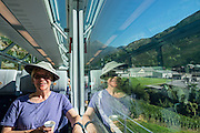 "Playfully, Switzerland advertises the Glacier Express as ""the slowest express train in the world."" Opened in 1930, this narrow gauge railway connects the mountain resorts of Zermatt and St. Moritz in the Swiss Alps, from the Matterhorn to Piz Bernina, frequently applying a rack-and-pinion system to go up and down steep grades. An especially curlycue portion of the Glacier Express route is honored as a UNESCO World Heritage Site: the ""Rhaetian Railway in the Albula / Bernina Landscapes"". Jointly operated by the Matterhorn Gotthard Bahn (MGB) and Rhaetian Railway (RhB), the 7.5 hour railway journey crosses 291 bridges, enters 91 tunnels and reaches 2033 m (6670 ft) elevation at Oberalp Pass. For licensing options, please inquire."