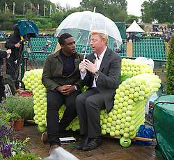 LONDON, ENGLAND - Monday, July 2, 2012: Boris Becker sits under an umbrella whilst working fot a television channel during day seven of the Wimbledon Lawn Tennis Championships at the All England Lawn Tennis and Croquet Club. (Pic by David Rawcliffe/Propaganda)