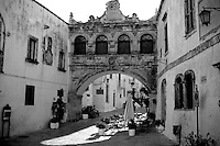 La piazza antistante la Cattedrale di Ostuni, sovrastata dal passaggio dall'Episcopio al palazzo del Seminario