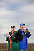 A couple with binoculars and a list look for birds at the Mad Island Preserve Christmas Bird Count.