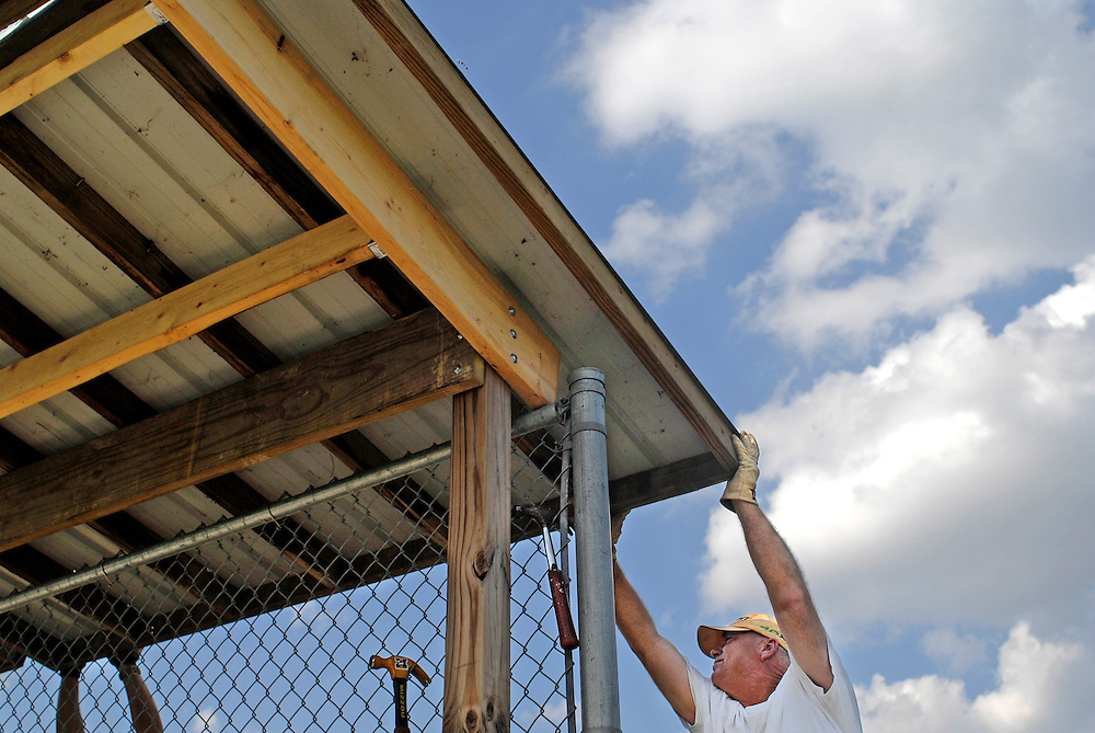 Horseshoes and hand grenades,&quot; Steve Humphreys jokes as he adjusts a roof panel on the dugout. He pulls the wood another inch to the left, then down, then up, trying to get it flush with another panel. Hammers hang from the chain link fence where bats normally hang. Ladders and drills, extension cords and screws litter the ground underneath the bench.<br /> <br /> Steve and two other Little League dads have taken off work the first day of fall to make a dent in the list of field improvements at the Daniel Boone Little League complex. &quot;We thought we'd spend some time together to do something good for the kids,&quot; says Kevin Harrison.<br /> <br /> College students help out with labor over the summer. &quot;Moms and dads do the work the rest of the year,&quot; Tim James explains.<br /> <br /> They've recycled the roof from the old Challenger Field dugout, stretching their $15,000 annual facilities budget a little further. They joke with each other as they secure the roofing in place. They talk about football. They brag about the league's accomplishments.<br /> <br /> In six hours, the job is done. The roof will protect the kids from the sun and foul balls. The league's 50th anniversary is next year, and they have plans for more improvements. The main concession stand needs work. The junior field dugouts are aging. With a day off here and there, the moms and dads are getting the job done.