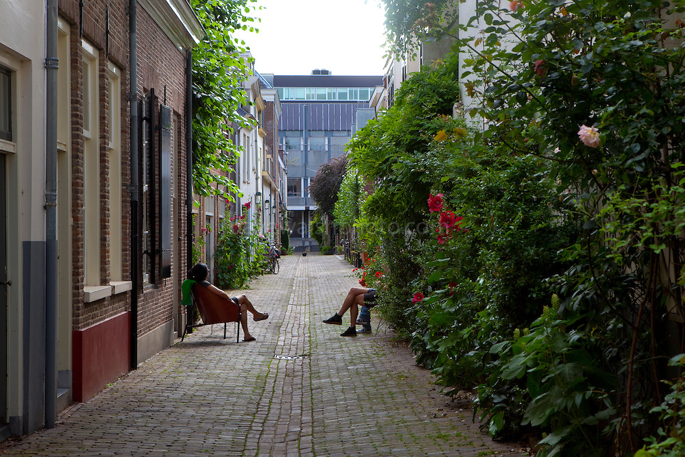 People enjoying the summer weather in an alleyway in Urecht, Netherlands