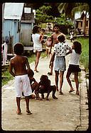 Boys play game of tossing soda bottle caps on sidewalk of slum in town of Eirunepe, Amazonas. Brazil