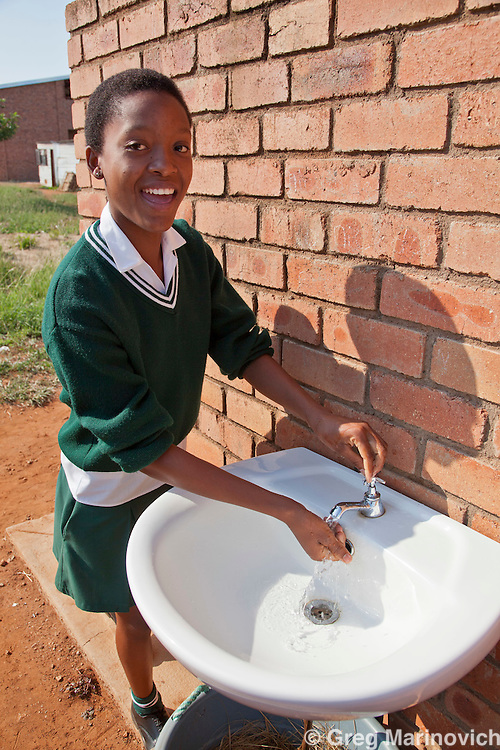 Phakama Trust, Nkomati district, Mpumalanga province, South Africa April 13, 2011: A girl washes her hands at the Sincobile Secondary School. The combination of urine diversion toilet system and Permaculture garden at Sincobile High School stands out to be the greatest achievement of the Inkomati project. The intention of this pilot project is that the local municipality and the Mpumalanga Provincial Government (and other responsible parties) will be able to duplicate the project in other schools and the community.   Photo Greg Marinovich.