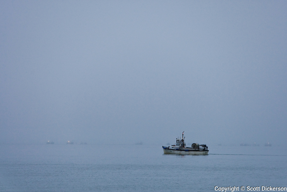 A commercial sockeye salmon fishing gillnet boat in thick fog on the Naknek River, Bristol Bay, Alaska.