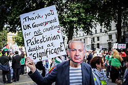 A pro-Palestinian protester wears a mask of Benjamin Netanyahu during a demonstration outside Downing street against arms sales to Israel. London Aug 2014