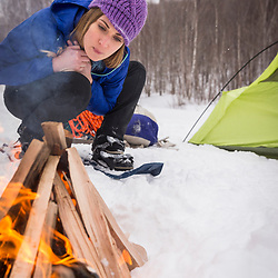 A woman carrying starts a fire while winter camping in New Hampshire's White Mountains. Randolph Community Forest.