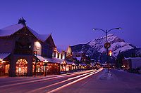 Shops along Banff Avenue at night (dusk) in winter, with Cascade Mountain in the background, Banff, Alberta, Canada