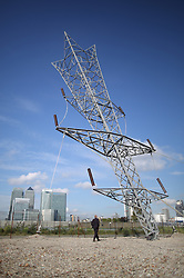 © Licensed to London News Pictures. 17/09/2015. London, UK. Artist Alex Chinneck inspects his newly unveiled 35 metre high sculpture entitled 'A bullet from a shooting star'.  Depicting an inverted electricity pylon, the artwork is located on Greenwich Peninsula. Photo credit: Peter Macdiarmid/LNP