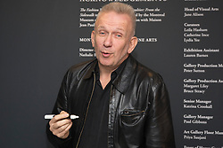 """© Licensed to London News Pictures. 8 April 2014. London, England. Pictured: Jean Paul Gaultier draws a head on the wall and signs it during a photocall. French fashion designer Jean Paul Gaultier opens his exhibition """"The Fashion World of Jean Paul Gaultier - From the Sidewalk to the Catwalk"""" at the Barbican Art Gallery, London. The exhibition runs from 9 April to 25 August 2014 and is organised by the Montreal Museum of Fine Arts in collaboration with Maison Jean Paul Gaultier, Paris.   Photo credit: Bettina Strenske/LNP"""