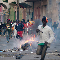 Men run un front of the police during protest in Dakar on February 18, 2012. Senegal riot police clashed with rock-throwing protesters today, firing teargas and water cannon for the fourth day running as fresh violence hit the capital a week before highly divisive polls. The opposition has been banned from protesting in central Dakar, leading to a second day of cat-and-mouse battles with police in the seaside capital who were trying to prevent them from gathering at Independence Square..©Sylvain Cherkaoui