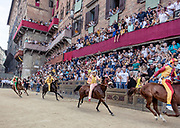 Italy, Siena, the Palio: from right Chiocciola, MOntone, Acquila , Selva. the final 100 meters of the last tour. At the shot of the mortaretto, the horses come out of the Entrone and line up at the starting line, known as the mossa. As soon as the last horse reaches the starting line the race begins and lasts for three rounds of the square (about 1 kilometre in total). The first horse to cross the finishing line is the winner, regardless of whether it is still mounted.