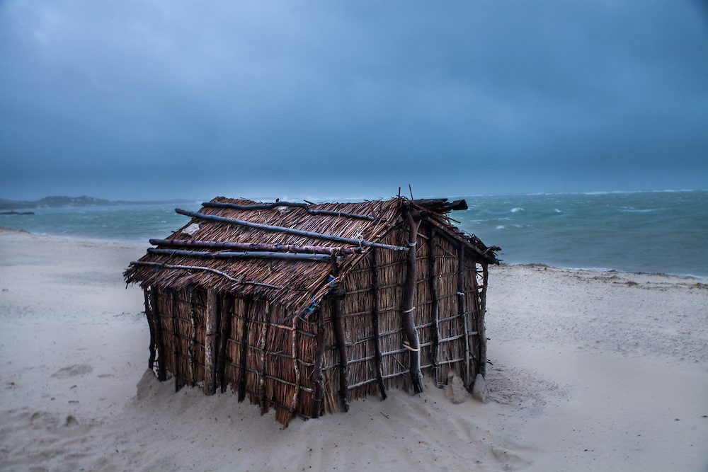 The house of a traditional fisher in southwest Madagascar is buffeted by strong winds hours before a cyclone was to hit the coast that night.  Traditional fishers are vulnerable to cyclones as they are not able to fish; the cyclone season coincides with increases in the price of rice; and wells are flooded, making it impossible to find clean drinking water.  Many traditional fishers migrate so that they are able to save enough money to live through the cyclone season.
