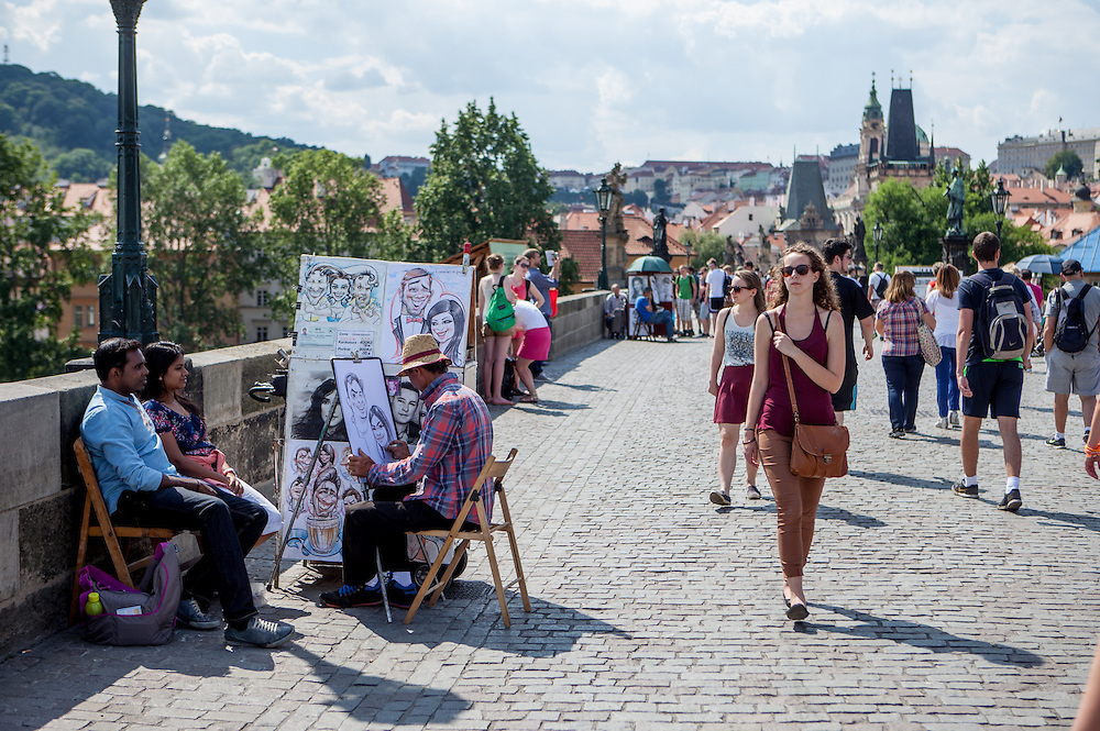 Portrait painter during a session with tourists at Charles Bridge.