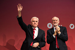 © Licensed to London News Pictures . 25/09/2017. Brighton, UK. Shadow chancellor JOHN MCDONNELL and JEREMY CORBYN embrace after McDonnell's speech at The Labour Party Conference at The Brighton Centre . Photo credit: Joel Goodman/LNP