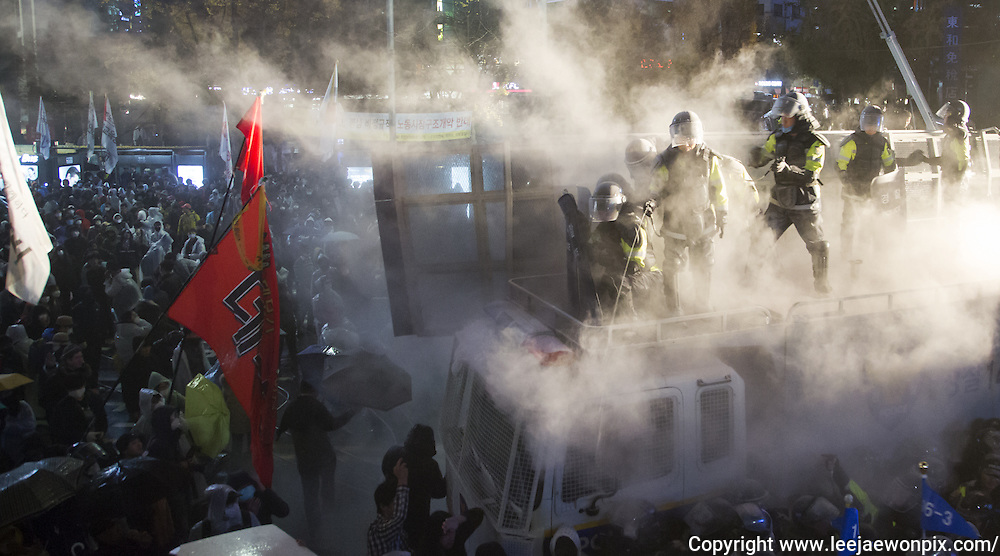 "Policemen spray liquid capsaicin and fire extinguisher toward protesters trying to march during an anti-government protest in central Seoul, South Korea, November 14, 2015. ""The People's Camp for Rising Up and Fighting"", representing various groups of farmers, students, workers and the poor, demonstrated to oppose South Korean government's plans to change the labor market and monopolize the authorship of history textbooks. Policemen set up vehicle barriers and used water cannon to break up people. The organizer said 130,000 people participated in the demo, while the police said 68,000 attended. Photo by Lee Jae-Won"