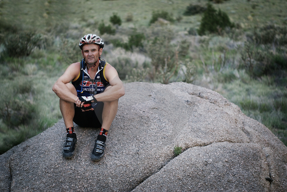 sandia mountain middle aged mountain biker man sitting portrait, sitting on a boulder resting, looking at camera, albuquerque, new mexico, horizontal composition