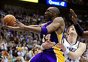 Los Angeles Lakers guard Kobe Bryant (24) is held by Utah Jazz center Kyrylo Fesenko during the second half of Game 4 of the NBA Western Conference second-round playoff series in Salt Lake City, Monday, May 10, 2010. (AP Photo/Colin E Braley)