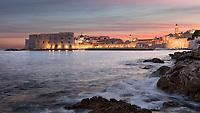 """Blick zur Stadtmauer und Altstadt von Dubrovnik bei Nacht. Die zum UNESCO-Weltkulturerbe gehört und den Beinamen """"Perle der Adria"""" trägt."""