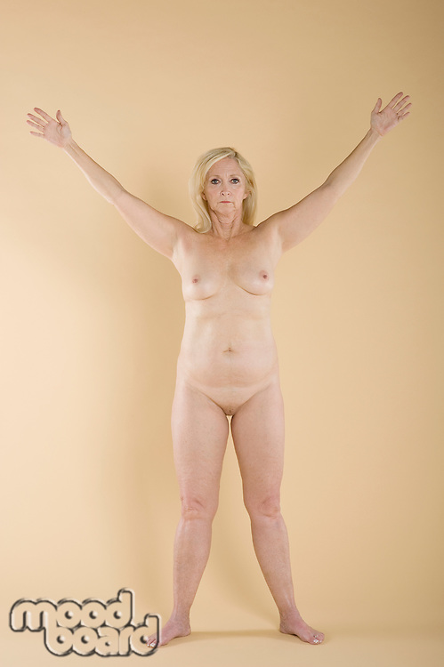 Portrait of naked woman with hands raised