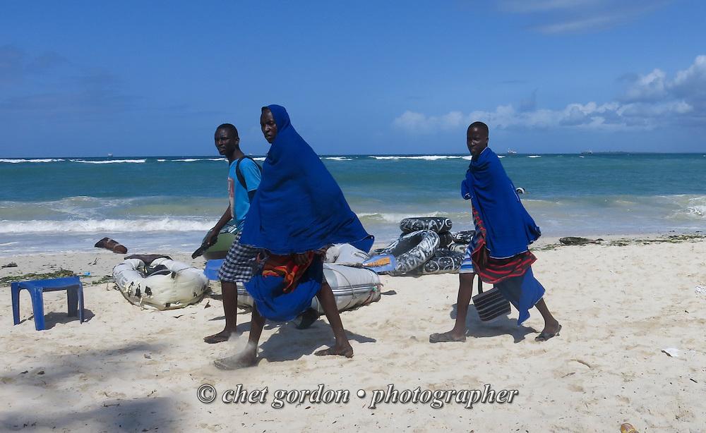 DAR ES SALAAM, TANZANIA.  Maasai tribesmen walk along Coco Beach in Dar es Salaam, Tanzania on Sunday, September 7, 2014.   © Chet Gordon/THE IMAGE WORKS