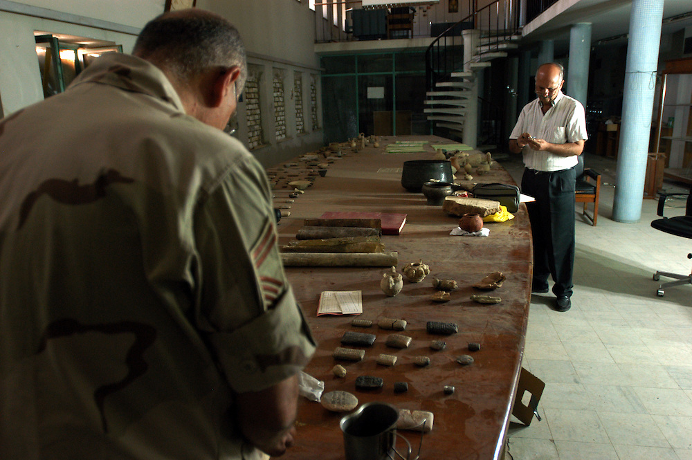 Dr. Ahmed Kamil, head of archeological expeditions in Iraq, and Puerto Rico Air National Guard officer Roberto Pinero, cataloguing looted artifacts returned to the Iraqi National Museum. US forces are conducting a recovery investigation at the museum..Baghdad, Iraq. 30 April 2003..Photo © J.B. Russell