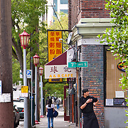 Chef at A & B Cafe takes cigarette break on corner outside restaurant, Chinatown, International District, Seattle, Washington