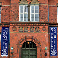 Odense Cathedral School in Odense, Denmark <br /> When I saw these banners flanking the door of the Odense Cathedral School I was intrigued to learn its history.  The Odense Katedralskole was established in 1283 as part of the St. Canute's Monastery.  Its mission was to teach young students subjects such as Latin and Greek in preparation for a life in the clergy. The high school moved into this renaissance building in 1894.