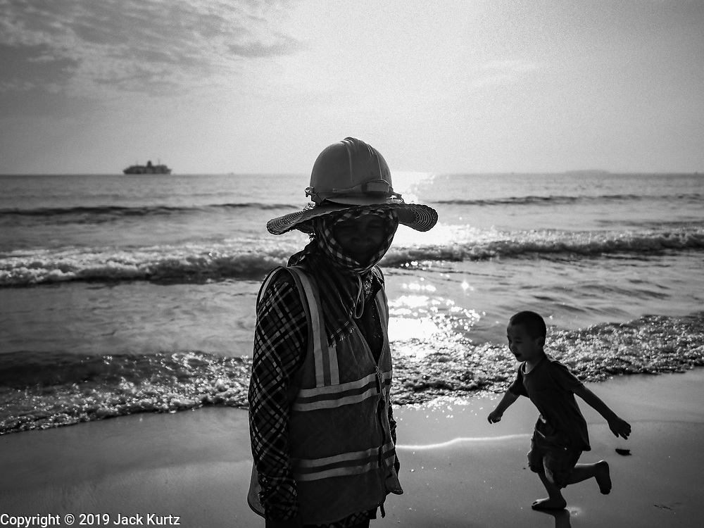 """12 FEBRUARY 2019 - SIHANOUKVILLE, CAMBODIA: A Cambodian construction worker walks past a Chinese tourist's child running down the beach near the Blue Bay resort development. Blue Bay is a Chinese casino and resort being built in Sihanoukville. There are about 50 Chinese casinos and resort hotels either open or under construction in Sihanoukville. The casinos are changing the city, once a sleepy port on Southeast Asia's """"backpacker trail"""" into a booming city. The change is coming with a cost though. Many Cambodian residents of Sihanoukville  have lost their homes to make way for the casinos and the jobs are going to Chinese workers, brought in to build casinos and work in the casinos.       PHOTO BY JACK KURTZ"""