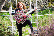 Woman with a guitar shaped flowerpot in her garden