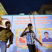 Young people dance on a stage set up in the middle of a slum during a celebration by Janodayam celebrating two high school students who achieved high grades. Saidapet, Chennai, India.