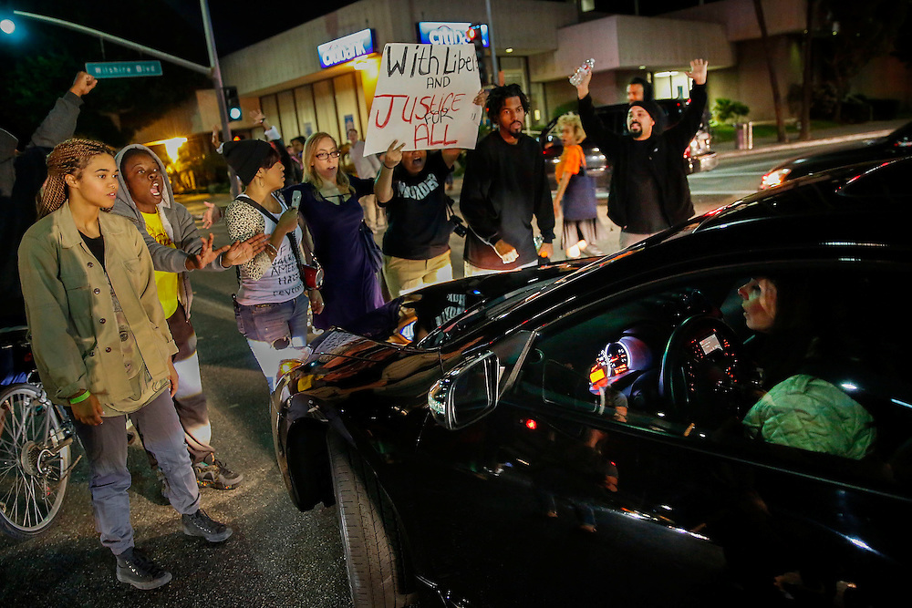 A woman drives through protestors as they blocked traffic while making their way down Wilshire Blvd to Rodeo Drive in Beverly Hills on Monday, November 24, 2014 in Beverly Hills, Calif. (Patrick T. Fallon/ For the Los Angeles Times)