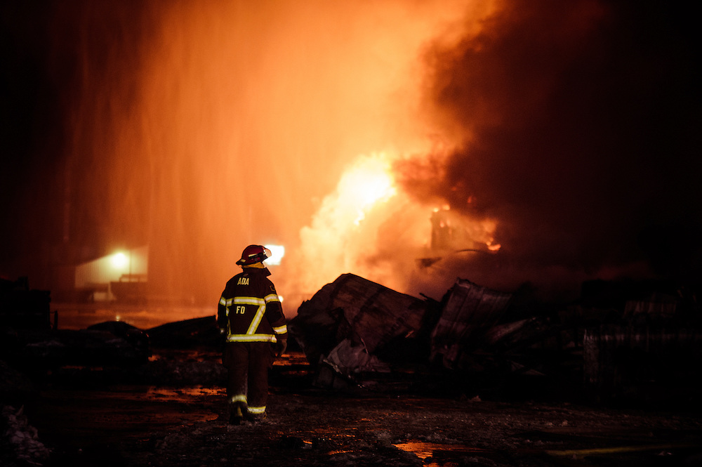 A firefighter surveys the grounds of the Triple Crown Nutrition elevator in Ada, Minn., during a fire which engulfed the building with 100-foot flames on January 3, 2013.
