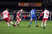 AFC Wimbledon midfielder Tyler Burey (32) taking on 3 Stevanage players during the EFL Trophy group stage match between AFC Wimbledon and Stevenage at the Cherry Red Records Stadium, Kingston, England on 6 November 2018.