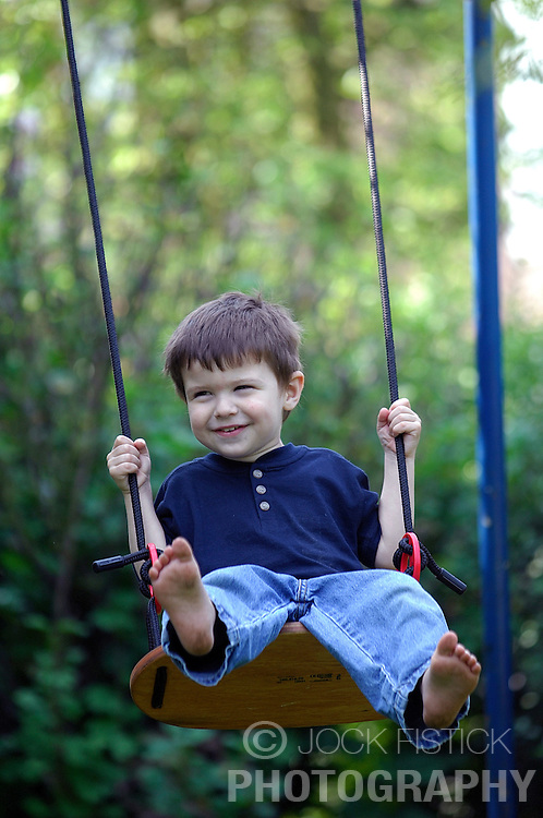 BRUSSELS, BELGIUM - APRIL-25-2007 - A happy smiling child on a swing. (PHOTO © JOCK FISTICK)