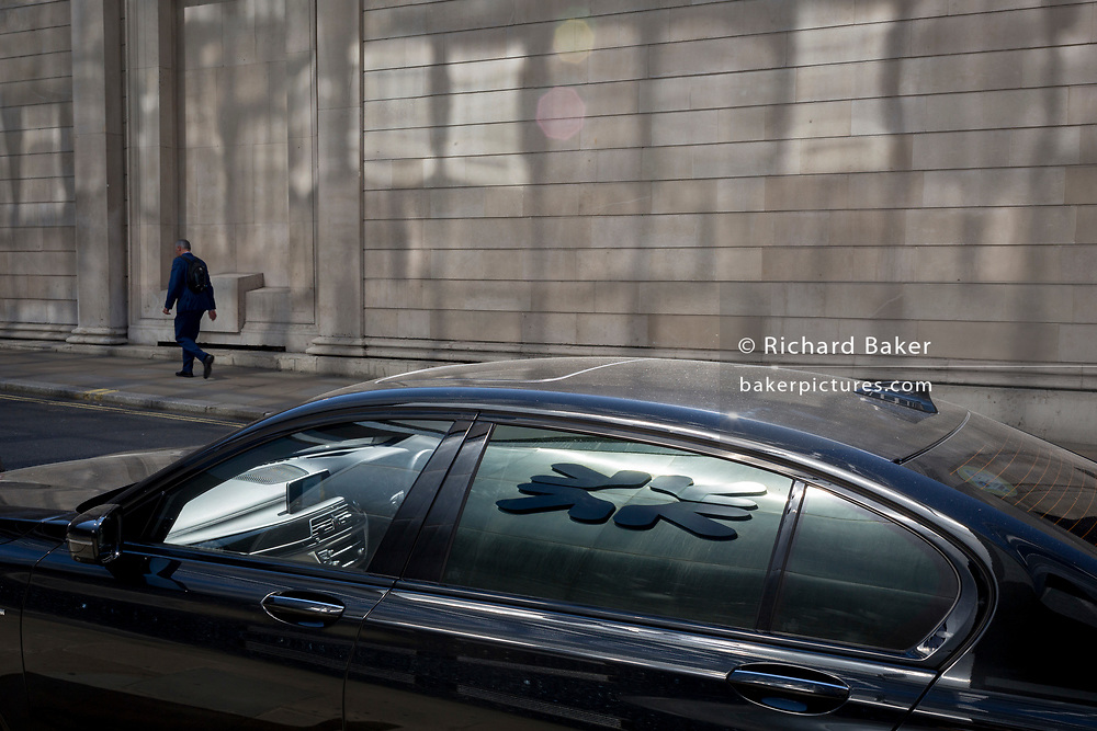With the logo of RBS reflected in the window of a car, a man walks slowly beneath the pillars and columns of the Bank of England in Bartholomew Lane in the City of London, the capital's financial district aka the Square Mile, on 15th May 2018, in London, UK.
