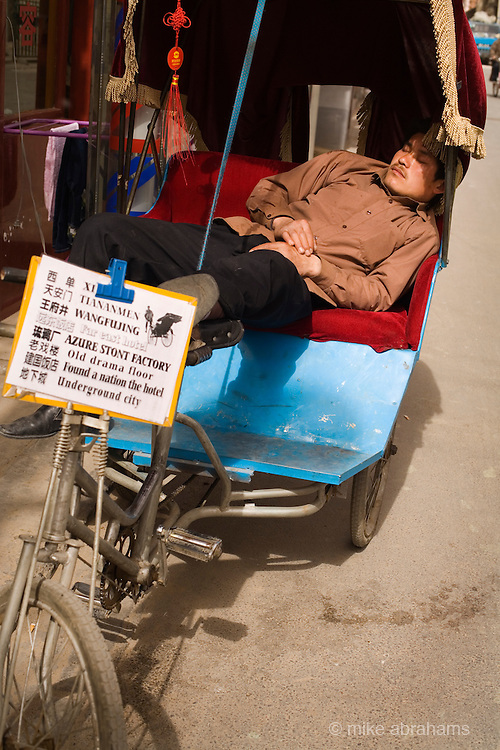 A man asleep on his rickshaw, Beijing, The People's Republic of China