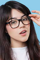 Close-up portrait of mixed race young woman wearing eyeglasses over blue background