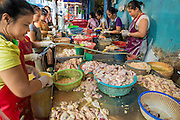 """26 SEPTEMBER 2012 - BANGKOK, THAILAND: Women package pieces of chicken at a stand in a Khlong Toey Market in Bangkok. Khlong Toey (also called Khlong Toei) Market is one of the largest """"wet markets"""" in Thailand. The market is located in the midst of one of Bangkok's largest slum areas and close to the city's original deep water port. Thousands of people live in the neighboring slum area. Thousands more shop in the sprawling market for fresh fruits and vegetables as well meat, fish and poultry.     PHOTO BY JACK KURTZ"""