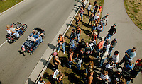 Residents and visitors alike line a downttown street to watch as Harley Davidson bikers roll through the city Friday Aug. 29, 2003 Milwaukee. Thousands of Harley Davidson bikers from all over the world came to Wisconsin to help celebrate Harley Davidson 100th anniversary.   photo by Darren Hauck