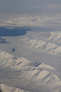 Aerial view in April of mountains and fjords covered in snow and ice in the arctic wilderness southern Spitsbergen island; Svalbard, Norway.