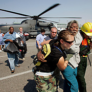 NEW ORLEANS, LA - September 4, 2005:  Evacuees are rushed off of helicopters that ferried them from various parts of flooded New Orleans to the Louis Armstrong International Airport on Sept, 4, 2005 in New Orleans following the destruction caused by Hurricane Katrina. The evacuees would within hours be put on planes and sent to cities around the country. (Photo by Todd Bigelow/Aurora)