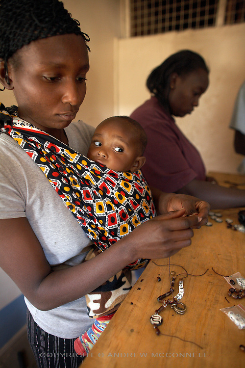 """Monica Waithira (24) and baby Ian Kimani (7 months), from the Korogocho slum, make key rings for the Italian fashion brand MAX&Co. in the Babadogo Community Centre, Nairobi, Kenya, on Monday, Jan. 12, 2009. Monica is a member of Bidii Shoe Makers, a team of 15 who create part of MAX&Co.'s """"ethical fashion"""" range in Africa. The key-rings were made by Bidii Shoe Makers, a small group of 15 people who were contracted to create part of MAX&Co.'s """"ethical fashion"""" range in Africa. The programme, in partnership with the ITC, is designed to reduce extreme poverty and empower women. Producing 30 - 50 key-rings per day the women can earn as much as $5 per day, much higher than the average wage for people in this part of Nairobi. The limited edition collection consists of one-of-a-kind handmade accessories such as shoulder-bags, bracelets, key-rings, belts and scarfs."""