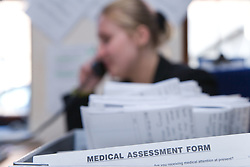 Recruitment applicant's Medical assessment form in foreground and woman on the telephone in the background,