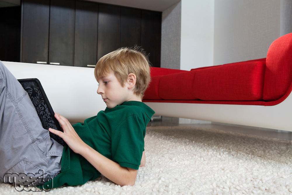 Side view of young boy using tablet pc while lying on rug