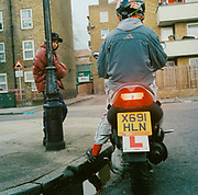 Teenage boy sitting on his scooter while another boy leans against a lampost L plates